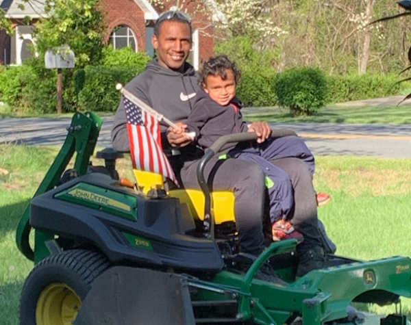 hope lawn care owner on lawn mower with son holding an american flag